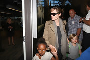 Angelina donned a neutral toned woven scarf while with her family at the airport.