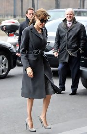 Angelina Jolie channeled Jackie O. in demure neutral pumps, a chic wool coat and oversize glasses.