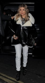 Fergie hid her growing baby bump with a leather and fur trimmed cape while out for dinner in London.