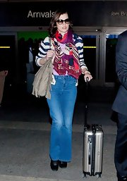 Milla Jovovich opted for a bright patterned scarf to top off her retro-inspired look.