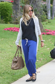 Sienna Miller styled her sporty outfit with a nude ostrich-leather hobo bag by Yves Saint Laurent.