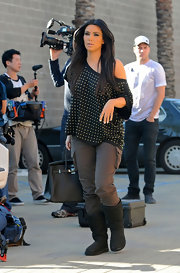 Kim wears an off-the-shoulder studded tee for this casual chic look.