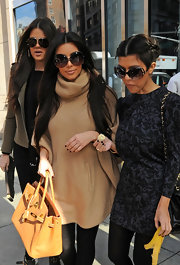 Kim paired her over sized sweater with large butterfly shades while out with her sisters in New York.