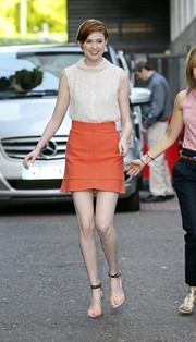 Karen Gillan flashed her slim legs in a red mini skirt with a fluted hem.