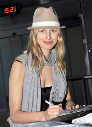 Karolina donned a tan fedora with a scarf for her trip to the airport.