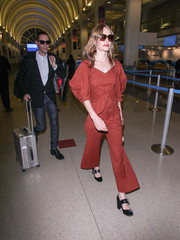 Kate Bosworth sauntered through LAX wearing a brick-red jumpsuit with puffed sleeves and a bowed waist.