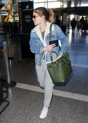 Kate Mara completed her airport look with an oversized green leather bag.