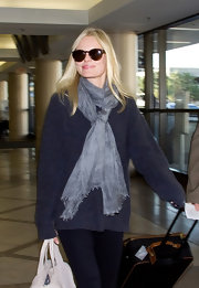 Kate dons a rustic gray blue winter scarf at the airport.