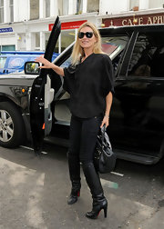 Kate Moss gave her monochromatic street style polish with a pair of black leather knee high boots.
