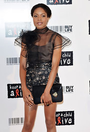 Naomie Harris paired her sheer overlay dress with a black envelope clutch with gold hardware.