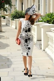 Kelly tops off an elegant black-and-white ensemble with a gorgeous statement hat.