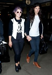 Kelly Osbourne slipped on a pair of round, white plastic sunglasses when she arrived at LAX.