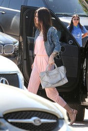 Kendall Jenner took a stroll looking cute in a cropped denim jacket layered over a pink jumpsuit.
