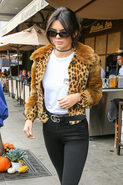 Kendall Jenner teamed a Gucci leather belt with black jeans and a fur jacket for a day out.