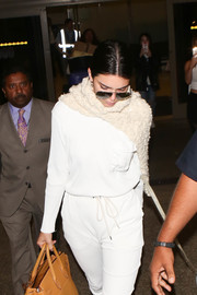 Kendall Jenner added extra warmth with a beige knit scarf.