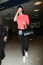 Kendall Jenner kept it comfy in a pink crop-top and black leggings while catching a flight.