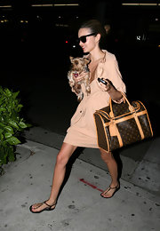 Miranda cares for her dog while wearing t-strapped flat sandals.