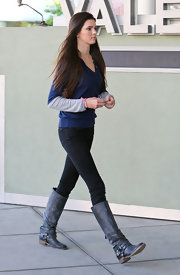 Kendall Jenner embraced layers wearing a navy v neck sweater over a gray long sleeved tee.