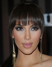 Kim Kardashian paired her sleek ponytail with gold dangle earrings.