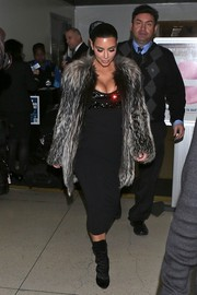Kim Kardashian caught a flight at LAX wearing a tight black Wolford dress.