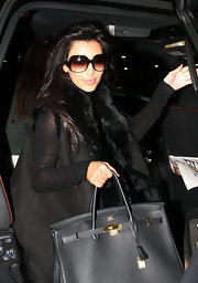 Kim K is dressed to kill in all black. She is wearing a fading lens sunglass that makes her look so good.