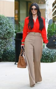 Kim Kardashian exuded effortless '70s glam in a poppy red blouse and oversize shades.