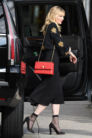 Kirsten Dunst punctuated her dark ensemble with a red chain-strap bag by Ferragamo.