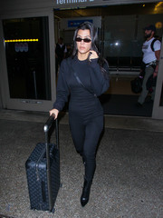 Kourtney Kardashian was spotted at LAX wearing a long-sleeve navy jumpsuit by Alexander Wang.