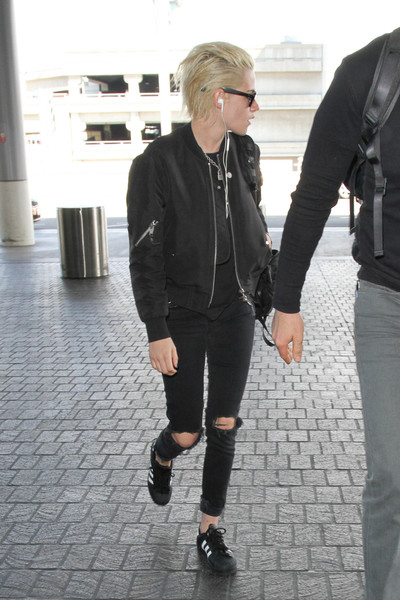 Kristen Stewart stayed comfy in a pair of Adidas sneakers while catching a flight.