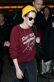 Kristen Stewart brightened up her outfit with a yellow knit beanie while catching a flight.