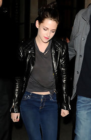 Kristen Stewart flashed a bit of skin in a knotted charcoal T-shirt.