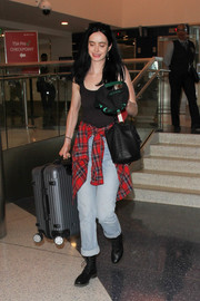 Krysten Ritter went for a grunge-chic airport look with this tank top, jeans, and plaid shirt combo.