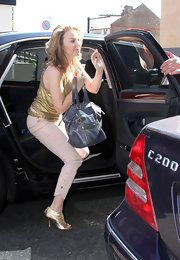 Singer Kylie Minogue stayed stylish while traveling to her managers office. She carried a gray leather tote bag.