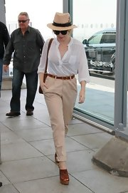 Kylie styled up her ensemble with a straw fedora at Heathrow airport.