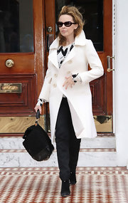 "Another day in West London and pop singer Kylie Minogue is seen making her way out of her home. She looked sophisticated in her white trench coat, which she topped off with a black leather ""Miss Sicily"" tote bag."