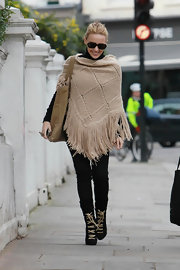 Kylie shows her street style once again in a beige knit poncho with luxe fringe.