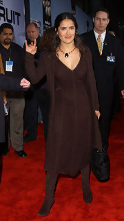 Salma Hayek paired her chocolate brown dress with a gemstone pendant necklace.