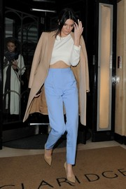 Kendall Jenner layered a beige Stella McCartney wool coat over her crop-top for a warmer finish.