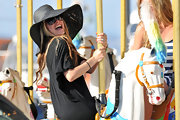 Avril laughs it up in her wide brimmed sunhat.