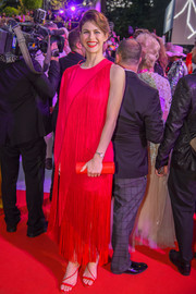 Alexandra Daddario sealed off her all-red ensemble with a tube clutch.