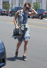 Lily Collins teamed her breezy dress with black broad-strap sandals by Sol Sana.
