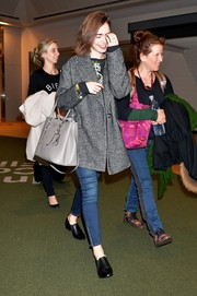 Lily Collins kept her airport look casual with a pair of zip-ankle skinny jeans by Paige.