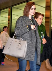 Lily Collins carried a stylish gray Prada handbag through an airport in Japan.