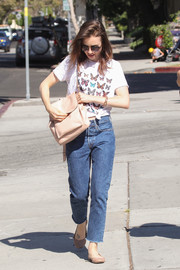 For her arm candy, Lily Collins chose a practical yet stylish nude leather backpack.