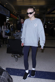 Lily-Rose Depp completed her comfy airport outfit with a pair of blue leggings.