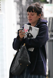 Lily showed off a cool quilted handbag while reading a text and holding a magazine.