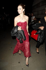 Lily James stunned in this red lace strapless dress matched with a leather jacket and black pumps.