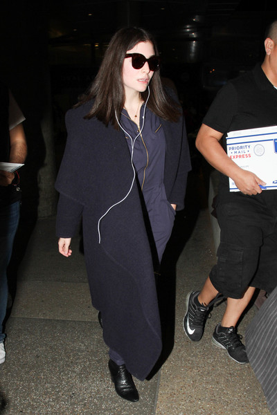 Lorde layered a black wool coat over a navy jumpsuit for a flight.