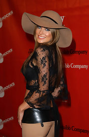Carmen Electra paired her lacy see-through top with a light tan wide hat at the Love Rock Charity Concert.