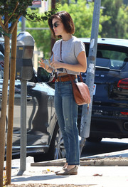 Lucy Hale accessorized with a classic brown messenger bag.